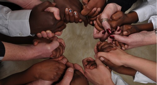 Diverse hands clasped in a circle
